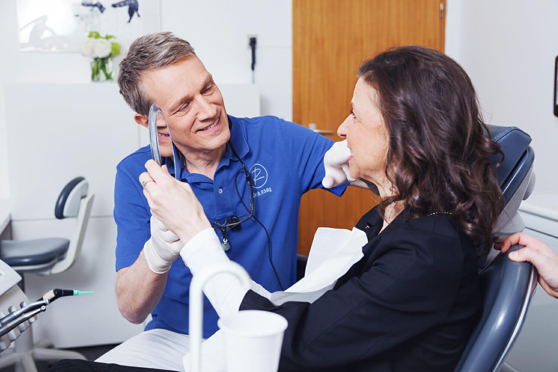Zahnarzt in Beratungssituation mit Patientin