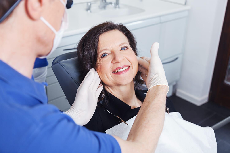 Lächelnde Patientin auf Behandlungsstuhl