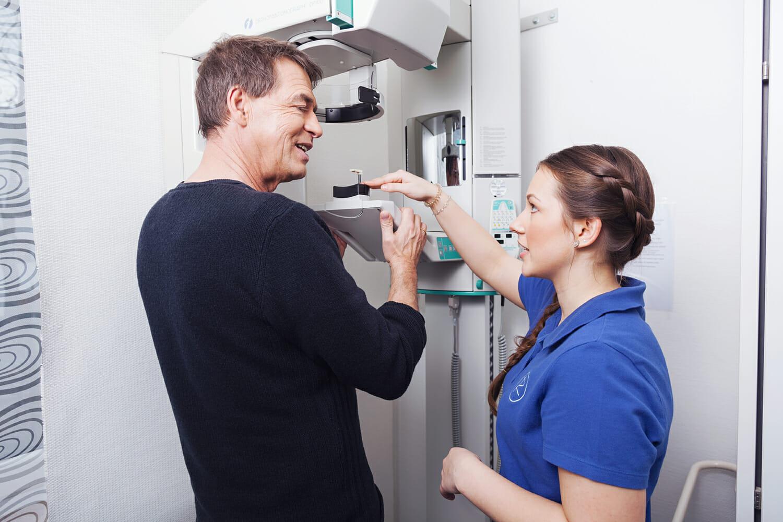 Patient erhält von Zahnarzthelferin Einweisung an Röntgengerät